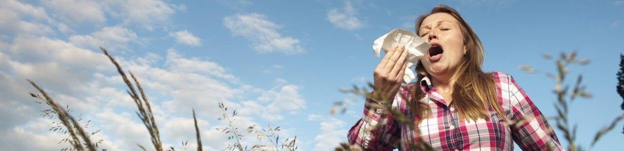 woman in a field sneezing