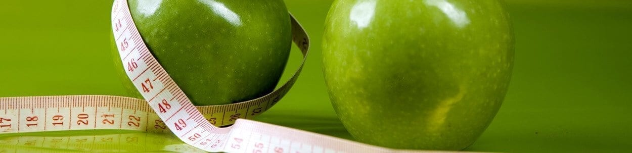 measuring tape around green apples