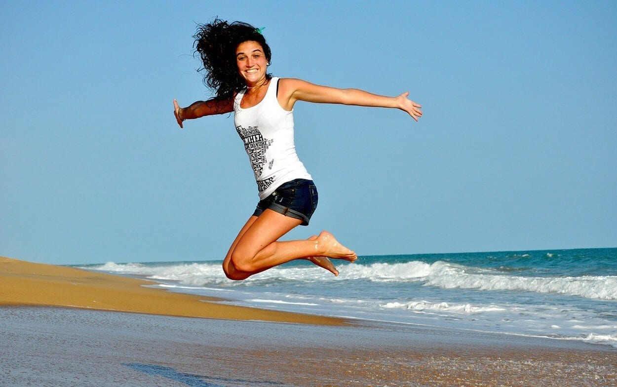 woman jumping at a beach