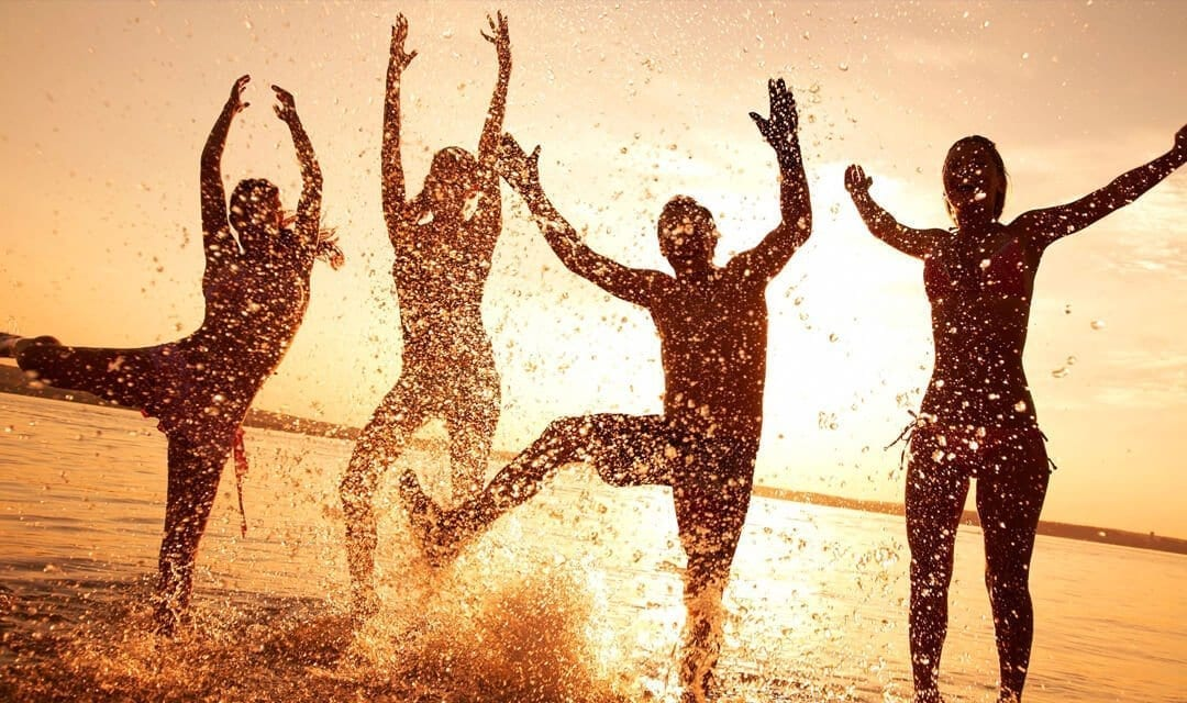 4 people splashing around at the beach
