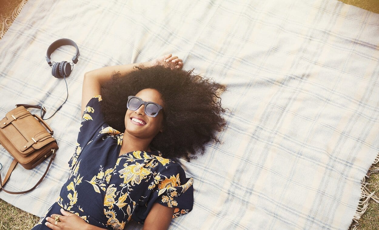 overhead view smiling woman with afro laying on blanket