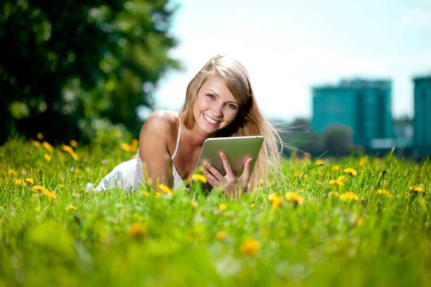 Girl in field with tablet studying