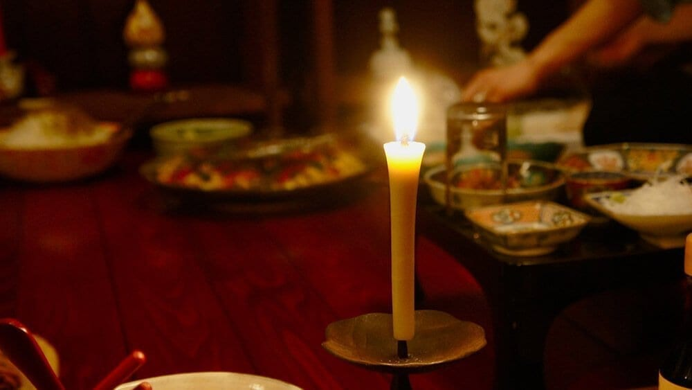 candle lighting a table of food