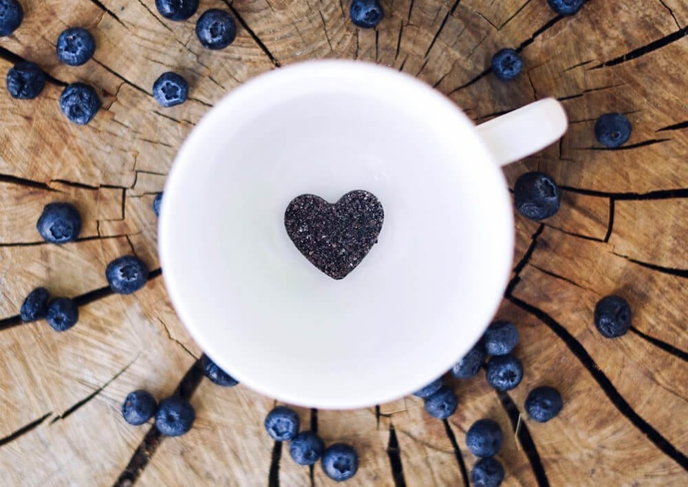 cup with blueberries spread around it