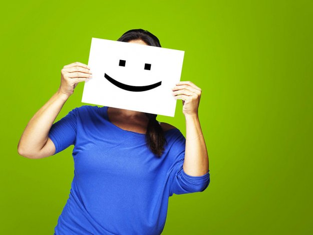 woman behind a smiley face board