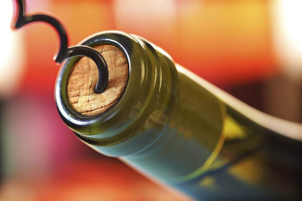 wine bottle being opened with a corkscrew