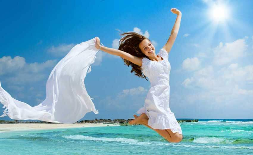 woman in a white dress jumping over at a beach