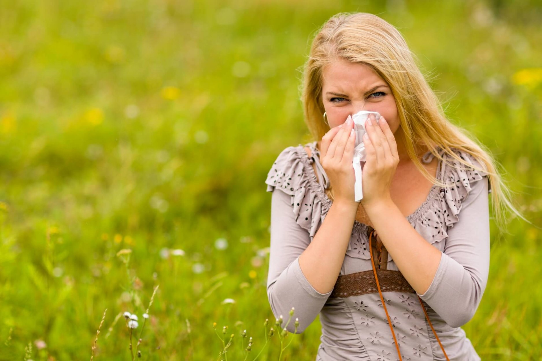 lady blowing her nose in a field